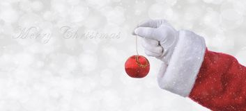 Santa Claus hand holding a red tree ornament over a silver bokeh background with snow effect. Banner size with copy space and the words Merry Christmas stock photo
