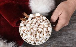 Santa Claus hand with a mug of hot chocolate next ot his traditional hat stock images