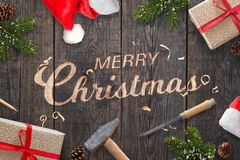 Santa Claus-Hand schnitzte Text der frohen Weihnachten auf Holzoberfläche mit Meißel und Hammer stockfotografie