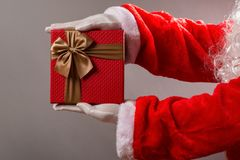 Santa Claus handing gift box with brown bow. Santa Claus handing a gift box with brown bow Royalty Free Stock Image