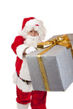 Santa Claus handing over a Christmas gift box Royalty Free Stock Photography