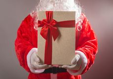 Santa Claus handing a white gift box with red bow. Santa Claus handing a white gift box with a red bow Royalty Free Stock Images