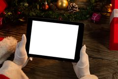 Santa Claus hands holding digital tablet. With Christmas ornament stock image