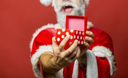 Santa Claus hands holding giftbox. Handsome man dressed as Santa Claus happy, smiling. Bearded santa claus with long stock image