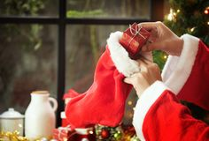 Santa claus hands are holding a Red gift or present box and Chri stock images