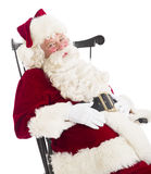 Santa Claus With Hands On Stomach Sitting On Chair. Portrait of Santa Claus with hands on stomach sitting on chair isolated over white background Royalty Free Stock Image