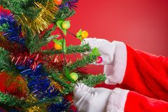 Santa Claus hanging flash lighting to fir tree. Santa Claus hanging flash lighting to a fir tree royalty free stock photography
