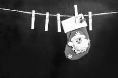 Santa Claus hanging on a wooden clothespin rope. On an original black background Royalty Free Stock Photo