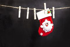 Santa Claus hanging on a wooden clothespin rope. On an original black background Royalty Free Stock Photos