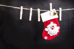 Santa Claus hanging on a wooden clothespin rope. On an original black background Royalty Free Stock Photography