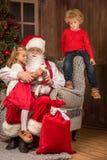 Santa Claus with happy children. Santa Claus sitting on grey armchair with happy children Stock Photography