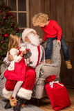 Santa Claus with happy children. Santa Claus sitting on grey armchair with happy children Stock Photos