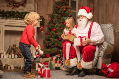 Santa Claus with happy children. Santa Claus sitting with happy children and looking their gift boxes Stock Images