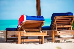 Santa Claus Hat on beach lounger with turquoise sea water and white sand. Christmas vacation concept. Santa Claus Hat on chair near tropical beach with turquoise royalty free stock photo