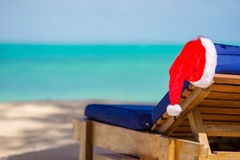 Santa Claus Hat on beach lounger with turquoise sea water and white sand. Christmas vacation concept. Santa Claus Hat on chair near tropical beach with turquoise stock images