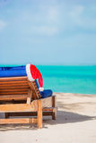 Santa Claus Hat on beach lounger with turquoise sea water and white sand. Christmas vacation concept royalty free stock photos