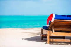 Santa Claus Hat on beach lounger with turquoise sea water and white sand. Christmas vacation concept. Santa Claus Hat on chair near tropical beach with turquoise royalty free stock photos