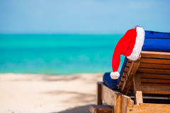 Santa Claus Hat on beach lounger with turquoise sea water and white sand. Christmas vacation concept. Santa Claus Hat on chair near tropical beach with turquoise stock photos