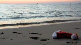 Santa Claus hat on beach at sunset. Human footprints on a sandy beach with Santa Claus hat at sunset stock footage