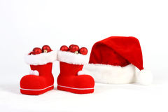 Santa Claus hat and boots with red and matt christmas balls on snow in front of white background Stock Photos