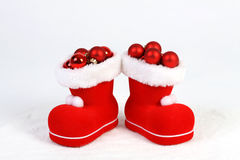 Santa Claus hat and boots with red and matt christmas balls on snow in front of white background Royalty Free Stock Photos