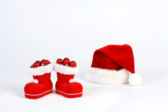 Santa Claus hat and boots with red and matt christmas balls on snow in front of white background Stock Images