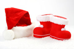 Santa Claus hat and boots on snow in front of white background Stock Photography