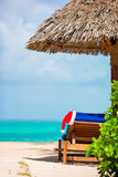 Santa Claus Hat on chair near tropical beach with turquoise sea water and white sand. Christmas vacation concept. Santa Claus Hat on chair near tropical beach royalty free stock photography