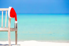 Santa Claus Hat on chair near tropical beach with turquoise sea water and white sand. Christmas vacation concept. Santa hat on chair longue at tropical caribbean stock image