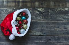 Santa Claus hat with christmas balls on rustic wooden background royalty free stock photography