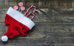 Santa Claus hat with Christmas candy. On background Stock Images