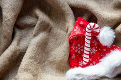 Santa Claus hat and Christmas candy cane. On jute background Royalty Free Stock Images