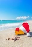 Santa Claus hat and christmas gift box on the seashore Royalty Free Stock Photo