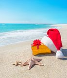 Santa Claus hat and christmas gift box on the seashore with sea Royalty Free Stock Photos