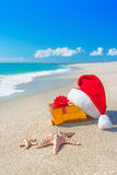 Santa Claus hat and christmas gift box on the seashore with sea Royalty Free Stock Photo