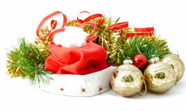 Santa Claus hat with Christmas ornaments. The red cap with a white pompom and fringes is in the midst of Christmas-tree garlands, red ribbon, green pine Royalty Free Stock Photos