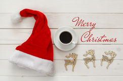 Santa claus hat, cup of coffee next to wooden decorations Stock Images