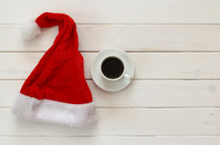 Santa claus hat, cup of coffee next to wooden decorations Stock Photography