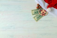 Santa Claus hat, 100 dollar bills, a piggy toy, a symbol of 2019, and Christmas toys on a wooden light background. Money concept royalty free stock image