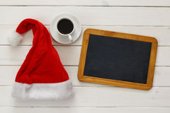 Santa claus hat, empty blackboard next to cup of coffee Stock Images