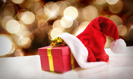 Santa Claus hat with gift golden background and diagonal view Stock Photography