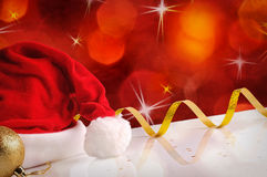 Santa Claus hat with golden ball and ribbon red background Stock Photo