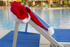Santa claus hat hanging on a sunbed near the pool Royalty Free Stock Photography