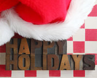 Santa Claus hat with happy holidays words. Happy holidays in old wood type on a checkerboard with a furry Santa hat Stock Images