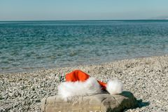Santa Claus hat lies on a large stone on the seashore. Santa went swimming stock photography
