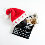 Santa Claus hat on a movie clapper board. And a film reel isolated on white background Stock Photo