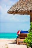 Santa Claus Hat op stoel dichtbij tropisch strand met turkoois zeewater en wit zand Het concept van de Kerstmisvakantie royalty-vrije stock fotografie