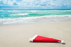 Santa Claus hat on seashore against waves Royalty Free Stock Image