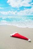 Santa Claus hat on seashore against waves Stock Image