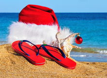 Santa Claus hat, slippers on the seashore Royalty Free Stock Photography